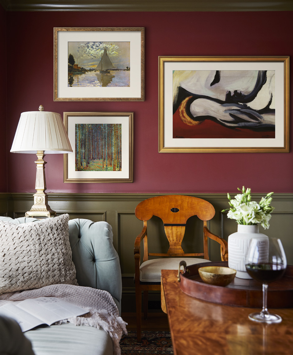 Red painted walls with framed art in cozy room with sofa and coffee table Sean Dagen Photography