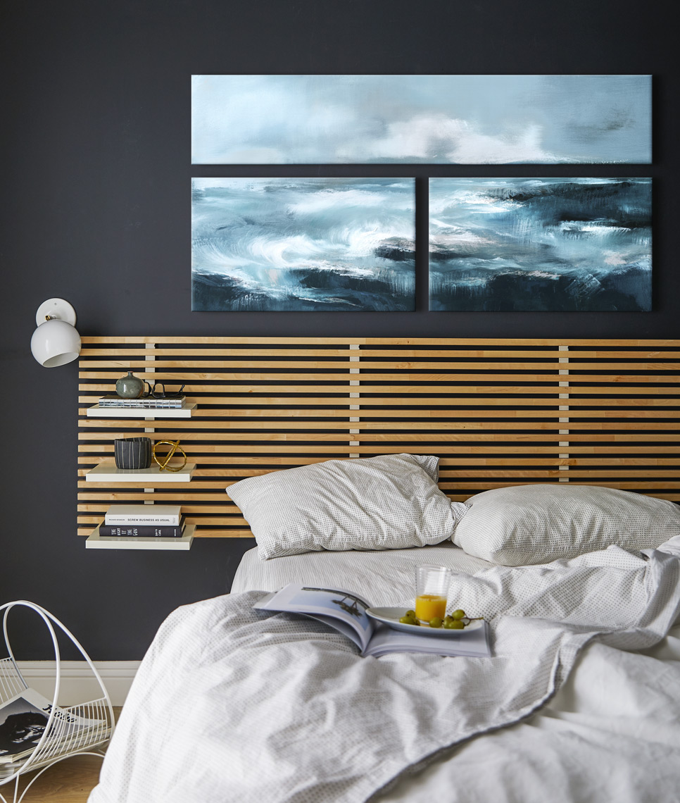 Bedroom with dark wall modern headboard messy bed white sheets under triptych painting on canvas Sean Dagen Photography