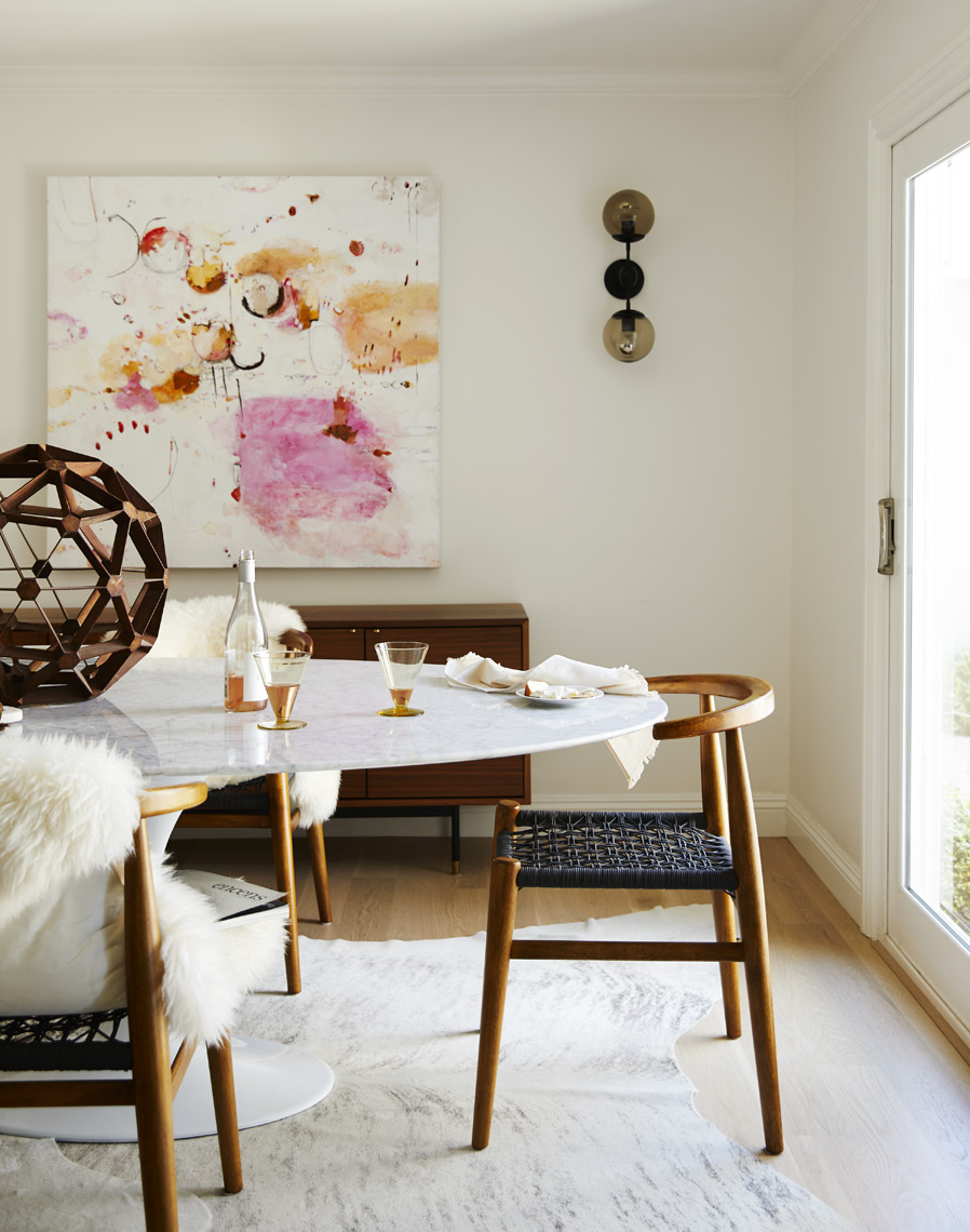 Modern dining room table and chairs with painting and modern sculpture and cow hide rug  Sean Dagen Photography