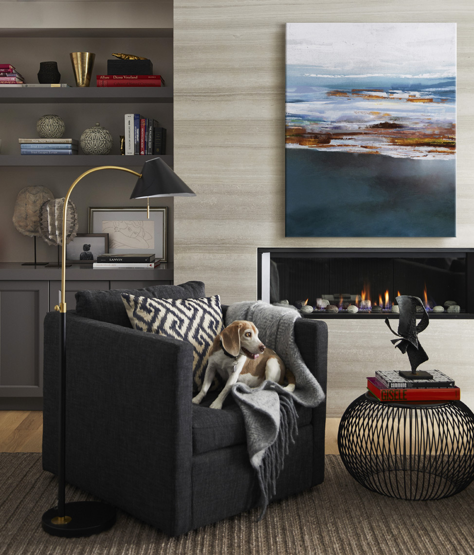 Dog on leather chair in front of modern fireplace with painting on mantle Sean Dagen Photography