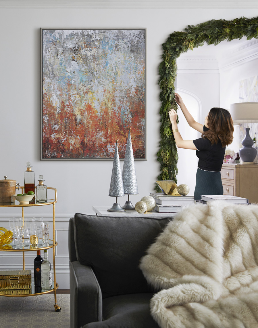 Woman decorating hanging garland in archway for the holidays with painting above bar cart in contemporary house