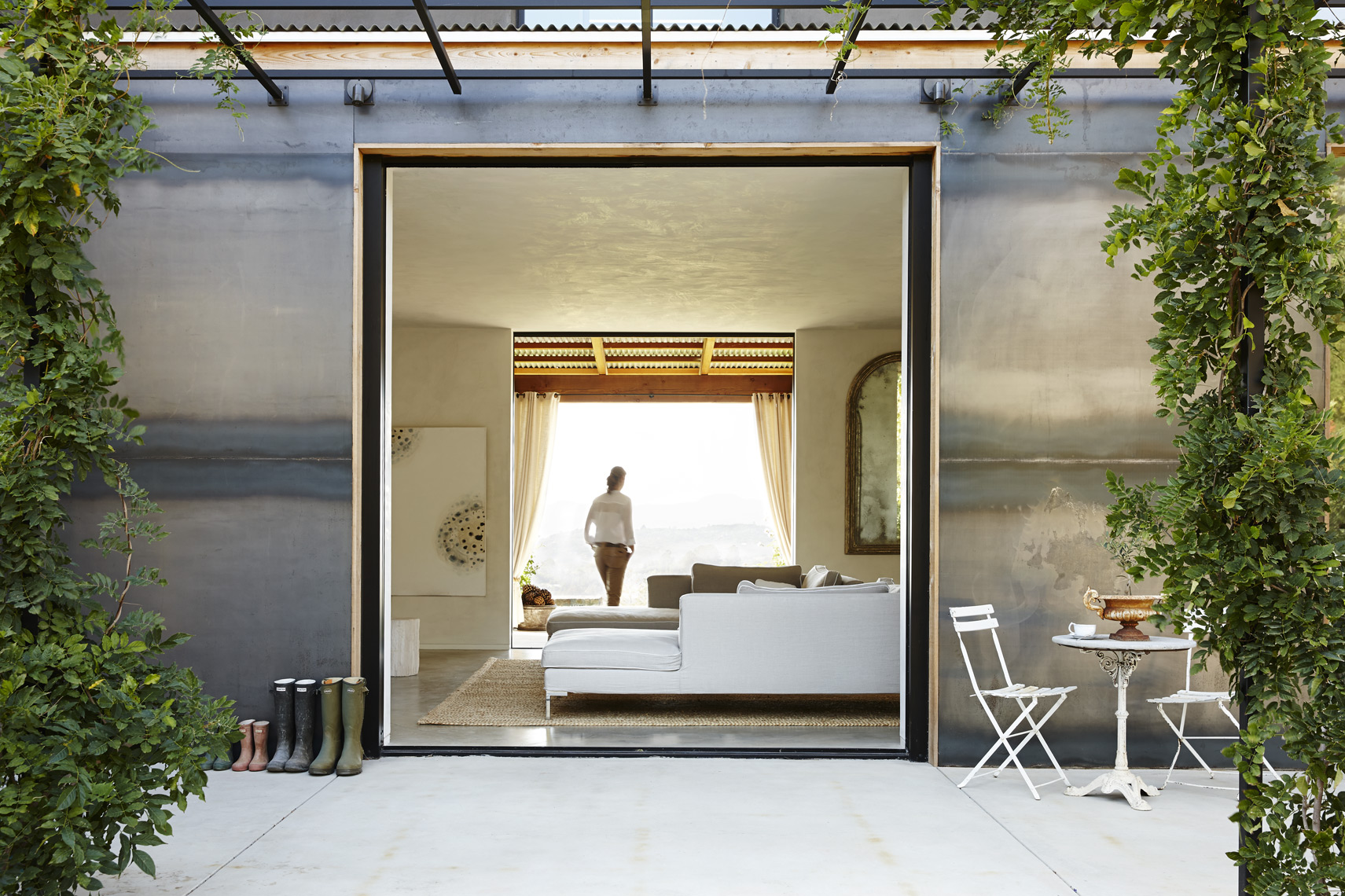 Exterior of modern house in Napa Valley with steel walls vines and woman walking through room Sean Dagen Photography
