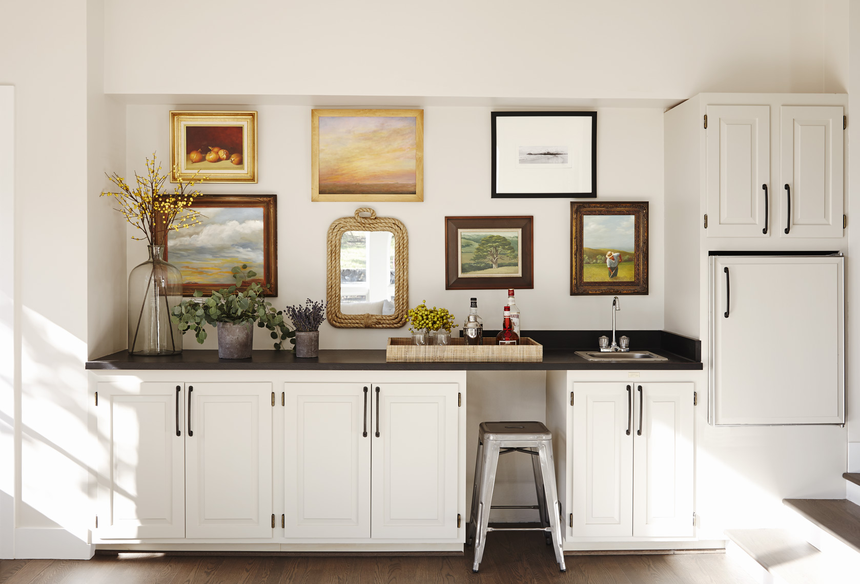 Bar with wall of framed art paintings and photographs in contemporary home Sean Dagen Photography