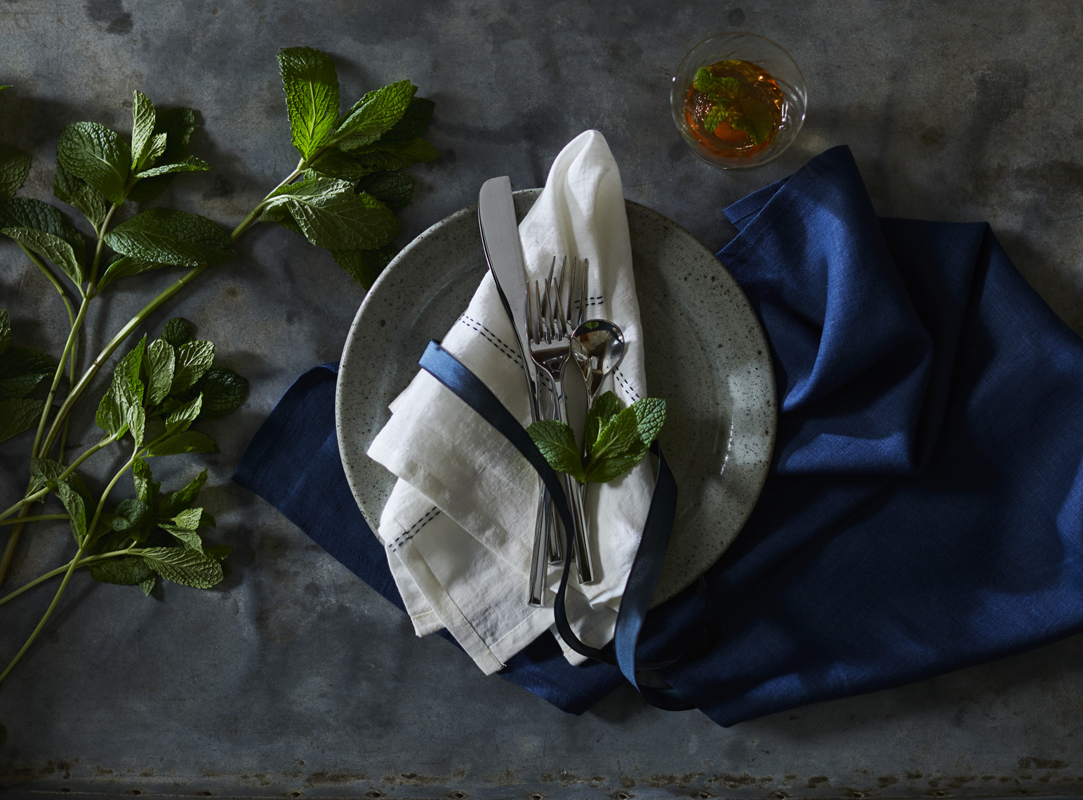 Polished silverware on linen napkin w/ greens and indigo napkin Sean Dagen Photography