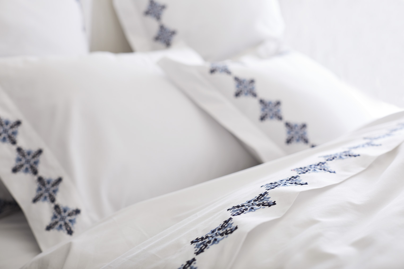 White pillows with blue pattern border on white bedding  Sean Dagen Photography