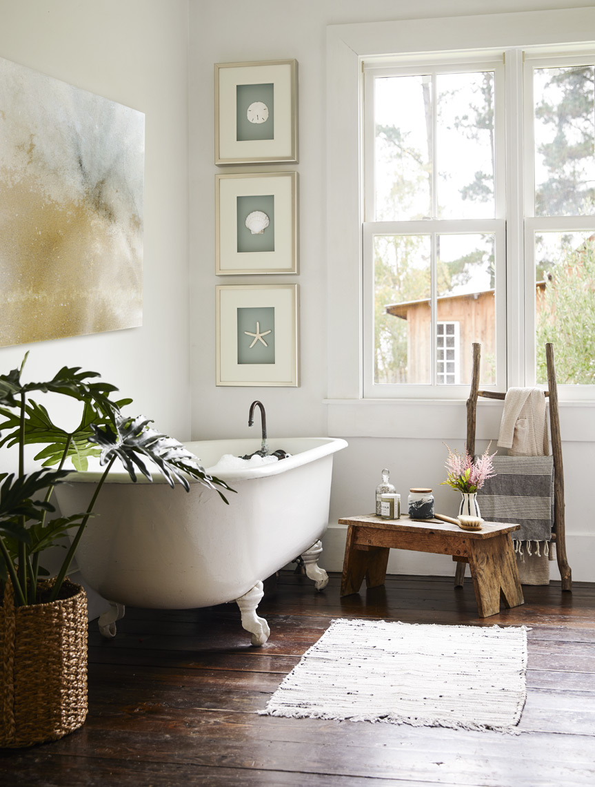 Farmhouse bathroom with framed art on wall potted plants clawfoot tub rustic floor