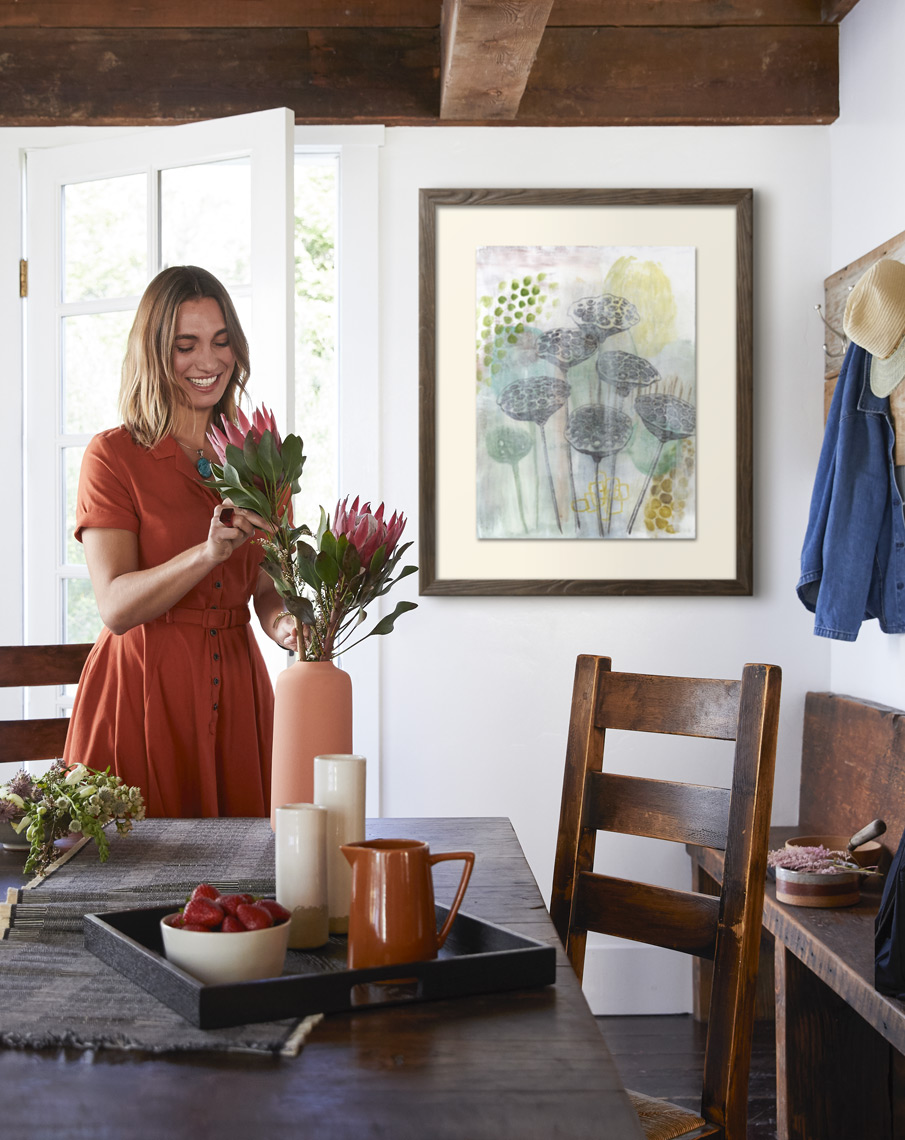 Woman making protea floral arrangement in vase with framed art print on wall in farmhouse dining room Sean Dagen Photography