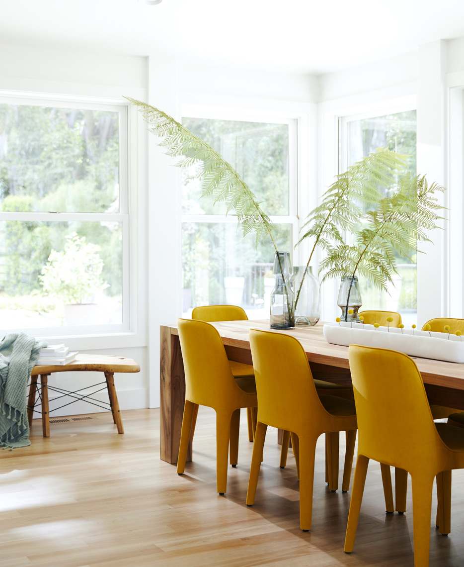 Mustard color chairs in modern dining room with a view