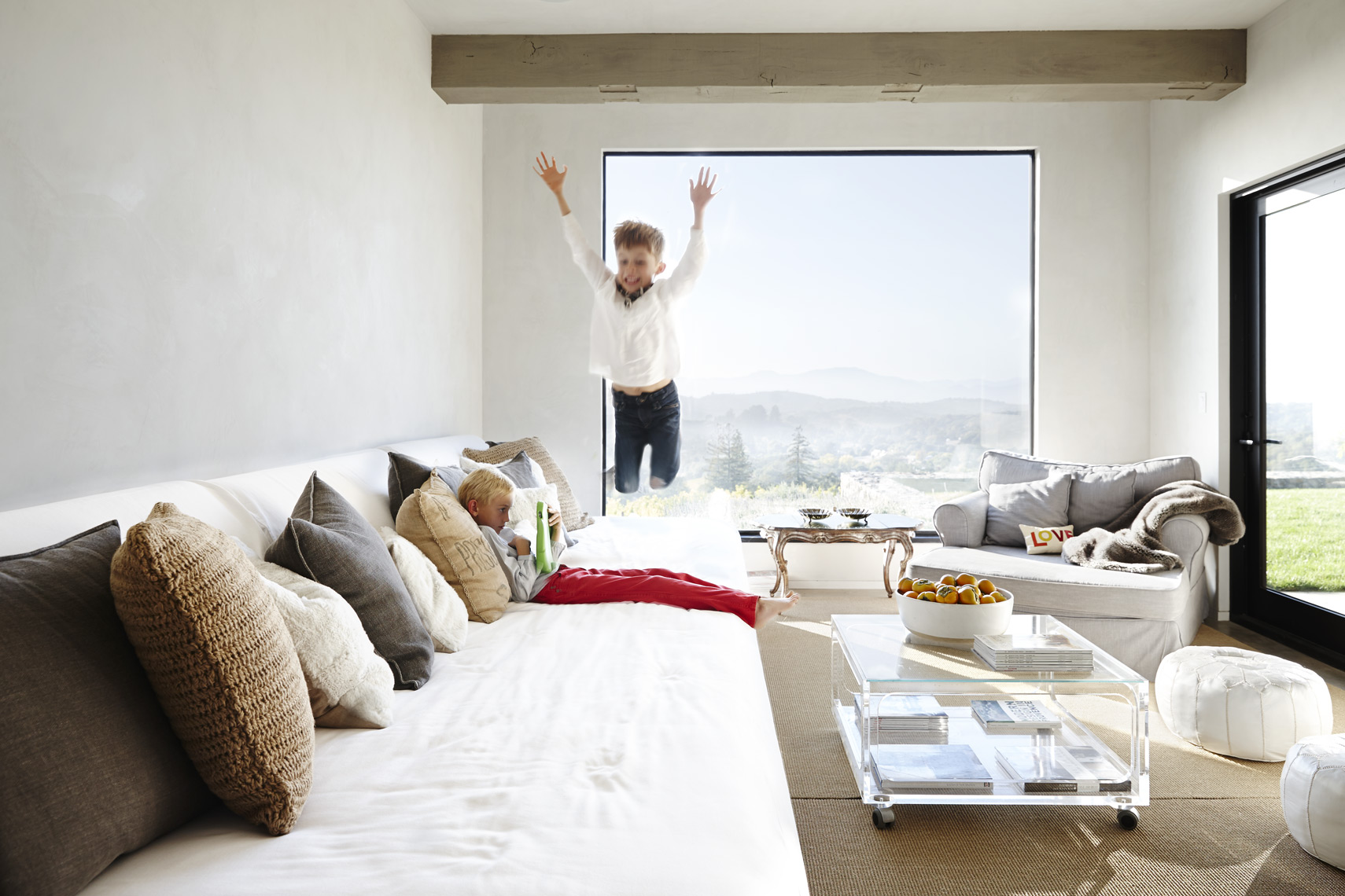 Child leaping over kid using ipad on sectional sofa in modern house Sean Dagen Photography