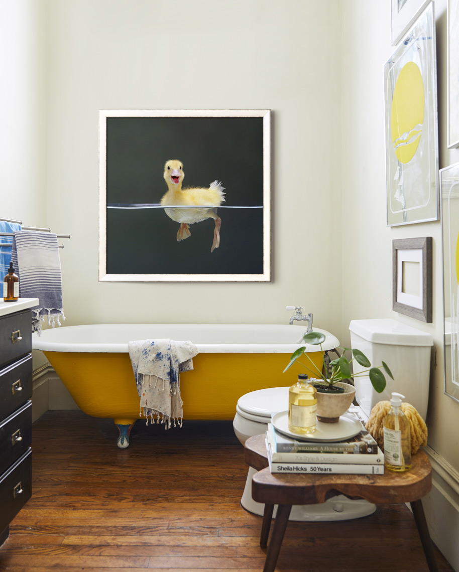 Bathroom with framed print of baby duck in water above bathtub
